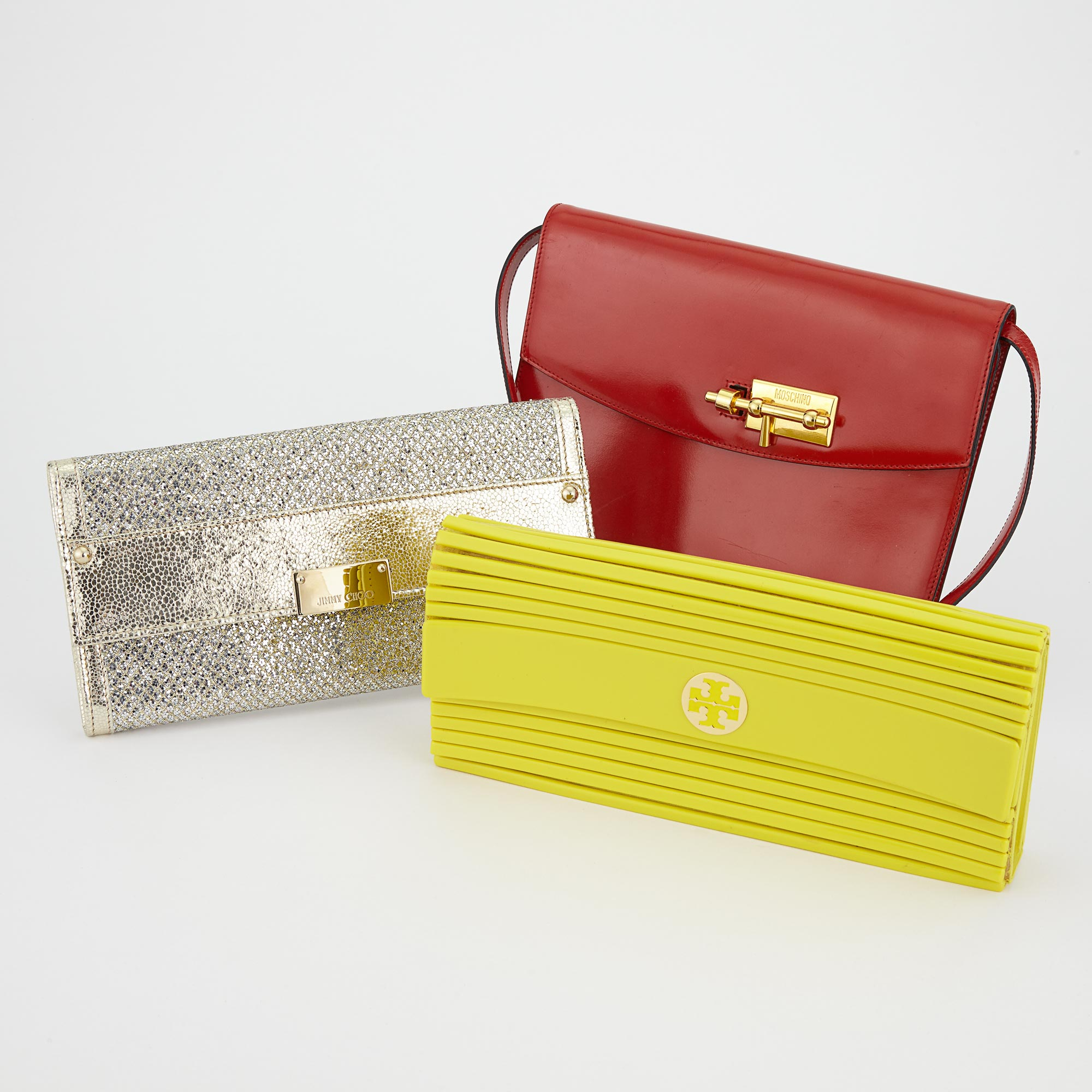 Lot image - Metallic Leather Clutch, Jimmy Choo, Red Leather Shoulder Bag, Moschino, and Yellow Acrylic Clutch, Tory Burch