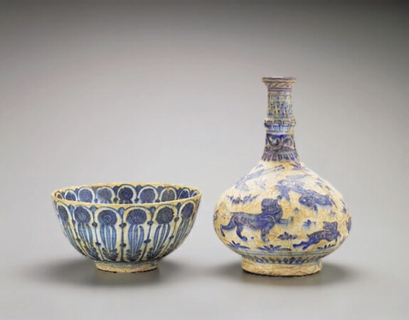 Lot image - PERSIAN BLUE AND WHITE POTTERY BOTTLE VASE AND BOWL  Probably 13th century and circa 17th century  Height 9 1/4 inches (23.5 cm); diame