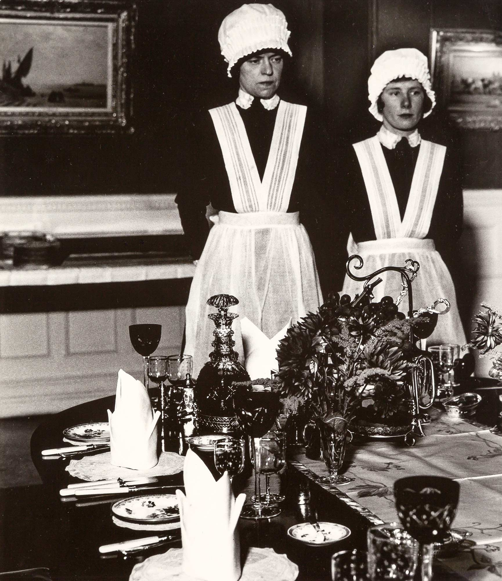 Lot image - BRANDT, BILL (1904-1983)  Parlourmaid and under-parlourmaid ready to serve dinner,