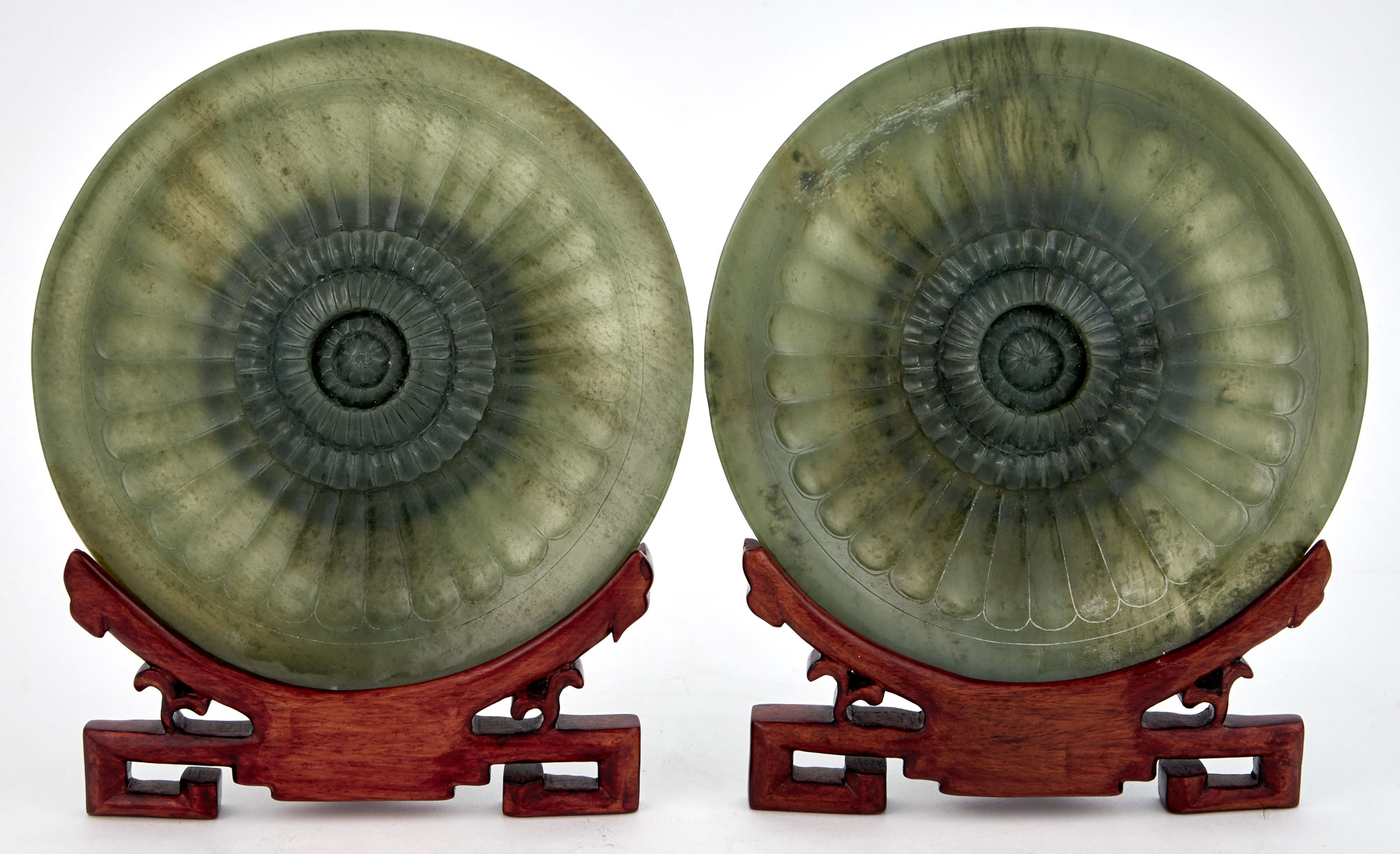 Lot image - Pair of Chinese Carved Green Hardstone Chrysanthemum Flowerhead-Form Plates and Hardwood Stands