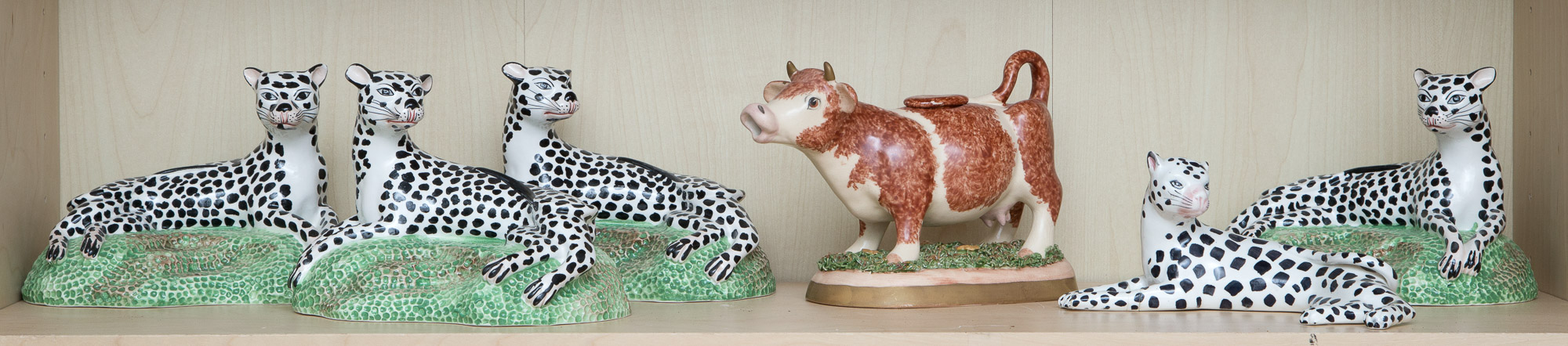 Lot image - Group of Five Pottery Leopard Figurines; Together with a Pottery Cow Creamer