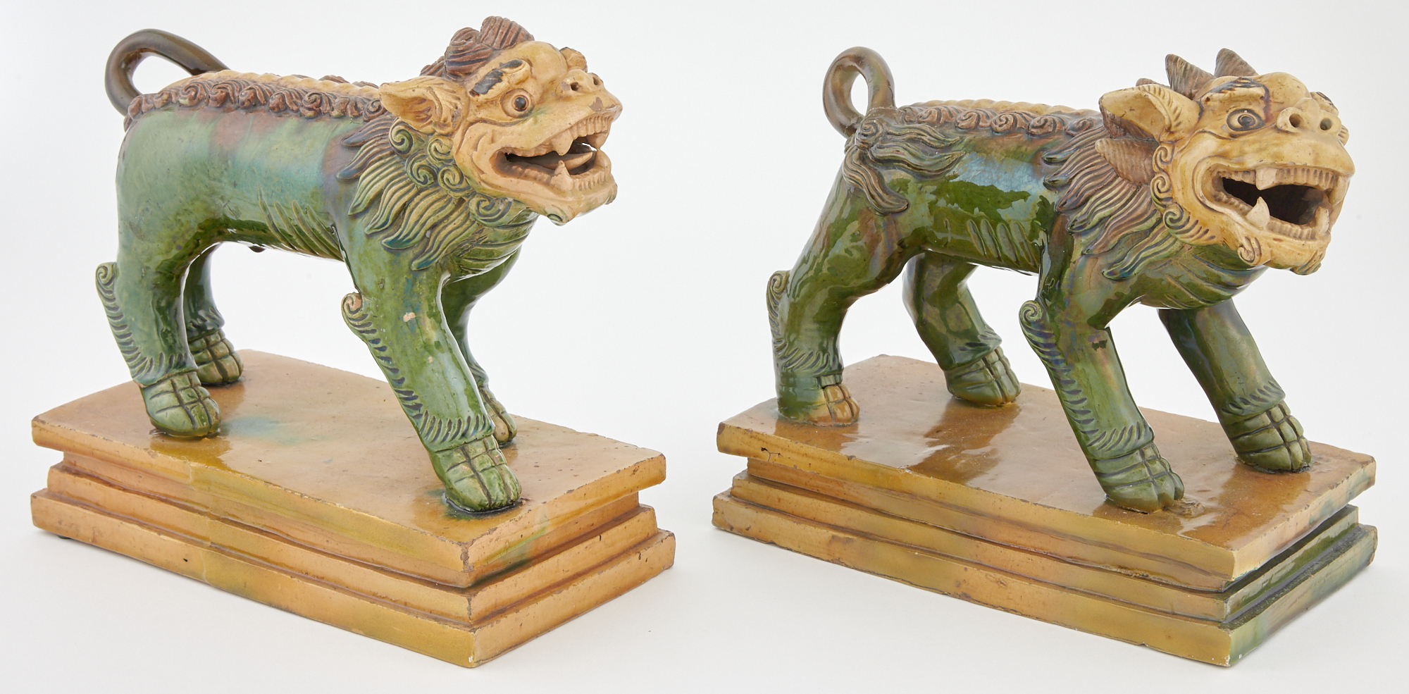 Lot image - Pair of Chinese Sancai Glazed Earthenware Models of Striding Fu Lions