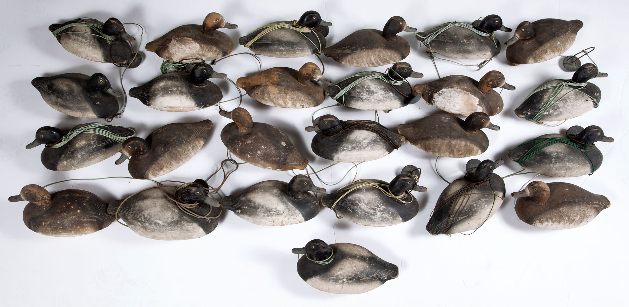 Lot image - LARGE GROUP OF BLUE BILL DUCK DECOYS IN PAIRS  25 carved and painted decoys of likely Blue Bill ducks in male-female pairs.