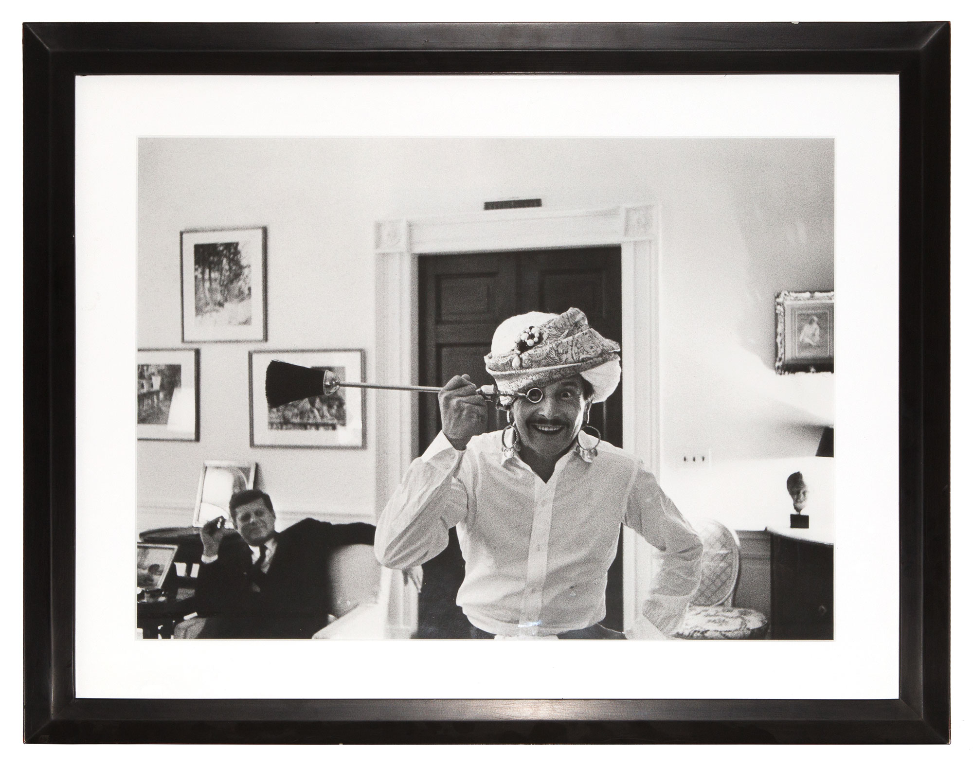 Lot image - GRAZIANI, BENNO  Large photograph depicting Oleg Cassini in a turban with President Kennedy in the background.