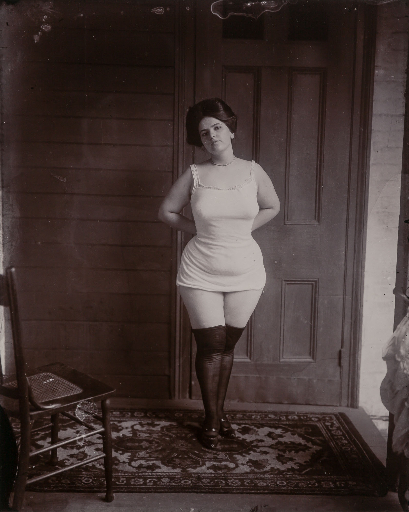 Lot image - BELLOCQ, E. J. (1873-1949)  [Storyville portrait, New Orleans, woman in underclothes standing on rug, about 1900]