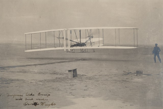 WRIGHT, ORVILLE  Inscribed photograph showing the first flight of the Wright Flyer I on December 17, 1903.